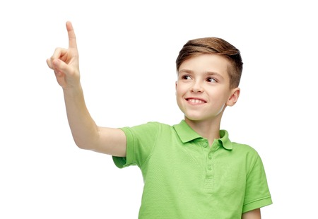 child finger: childhood, fashion and people concept - happy smiling boy in green polo t-shirt pointing finger up
