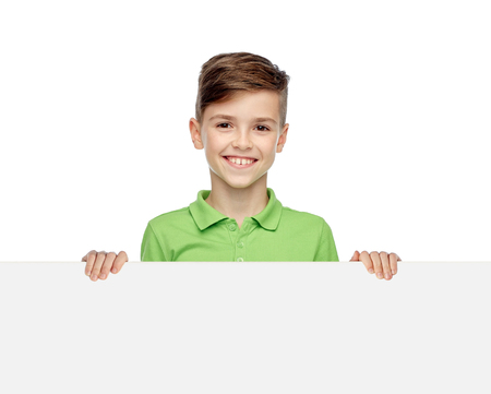 ten empty: childhood, advertisement and people concept - happy smiling boy in green polo t-shirt holding white blank board