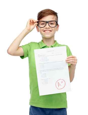 test result: childhood, school, education and people concept - happy smiling boy in eyeglasses holding paper with test result