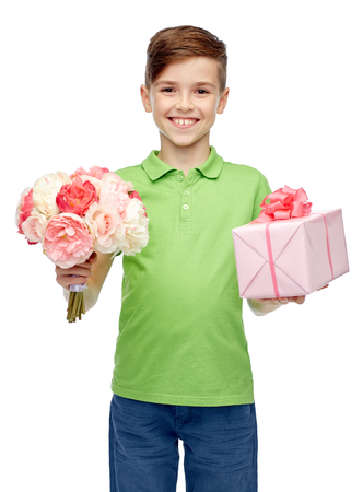 childhood, holidays, presents and people concept - happy boy holding flower bunch and gift box Stock Photo