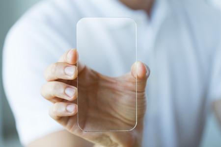 テクノロジー: ビジネス、技術と人のコンセプト - 押しながらオフィスで透明なスマート フォンを示す男性の手のクローズ アップ