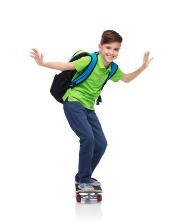 childhood, leisure, school and people concept - happy smiling student boy with backpack riding on skateboard