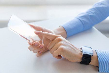 business technology: business, technology and people concept - close up of woman hand holding and showing transparent smart phone and watch at office