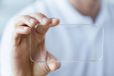 futuristic man: business, technology and people concept - close up of male hand holding and showing transparent smartphone at office Stock Photo