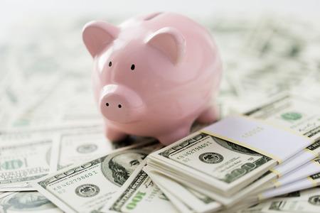 Wirtschaft, Finanzen, Investitionen, Einsparung und Korruption Konzept - Nahaufnahme von Dollar Bargeld und Sparschwein auf dem Tisch Lizenzfreie Bilder