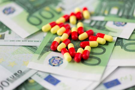 droga: la medicina, las finanzas, la salud y el tr�fico de drogas - p�ldoras m�dicas o drogas y dinero efectivo en euros en la mesa Foto de archivo