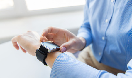 business technology: business, technology and people concept - close up of woman hands setting smart watch at office Stock Photo