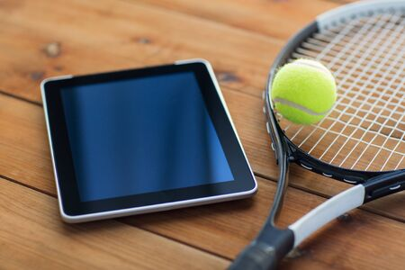 computer clubs: sport, fitness, technology, game and objects concept - close up of tennis racket with ball and tablet pc computer on wooden floor