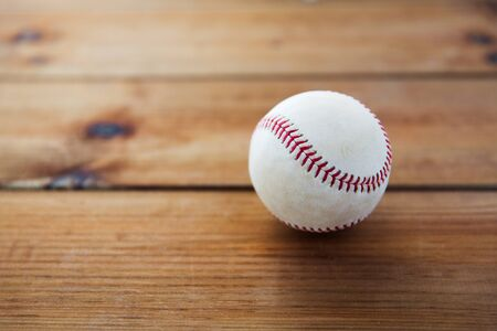 baseball stuff: sport, fitness, game and objects concept - close up of baseball ball on wooden floor