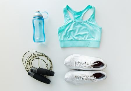 sport, fitness, gezonde leefstijl, cardio training en objecten concept - close-up van vrouwelijke sportkleding, springtouw en fles set Stockfoto
