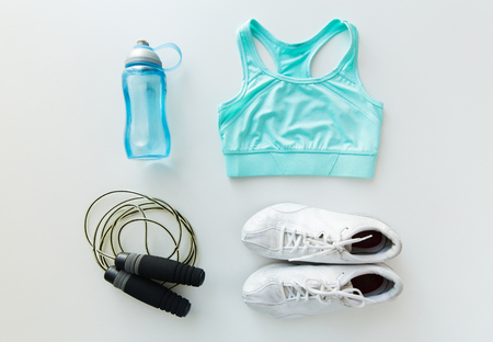 sport, fitness, healthy lifestyle, cardio training and objects concept - close up of female sports clothing, skipping rope and bottle set Archivio Fotografico