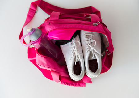 sport, fitness, healthy lifestyle and objects concept - close up of female sports stuff in backpack and dumbbells