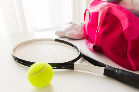 sport, fitness, healthy lifestyle and objects concept - close up of tennis racket and balls with female sports bag Banco de Imagens