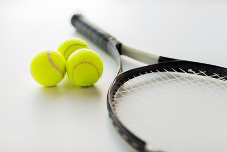 tennis balls: sport, fitness, healthy lifestyle and objects concept - close up of tennis racket with balls