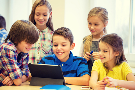 education, elementary school, learning, technology and people concept - group of school kids with tablet pc computer having fun on break in classroom 版權商用圖片 - 51242741