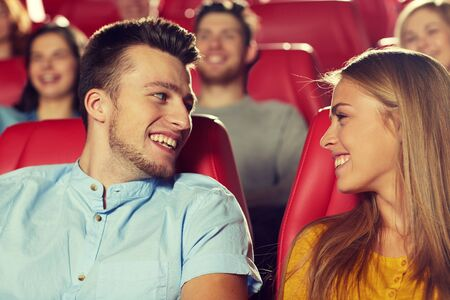 at the theater: cinema, entertainment and people concept - happy friends watching movie and talking in theater Stock Photo