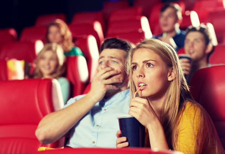 family movies: cinema, entertainment and people concept - couple drinking soda and watching horror, drama or thriller movie in theater