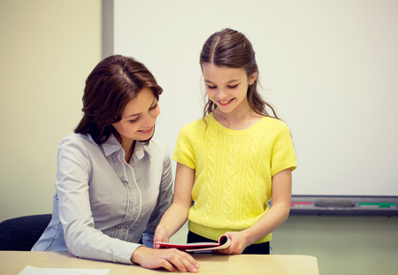 school notebook: education, elementary school, learning, examination and people concept - school girl with notebook and teacher in classroom Stock Photo