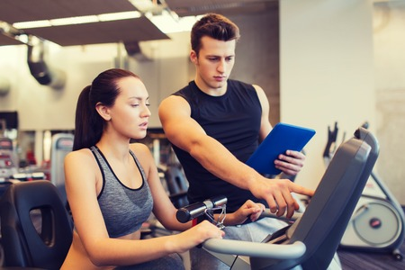 trainers: sport, fitness, lifestyle, technology and people concept - woman with trainer working out on exercise bike in gym