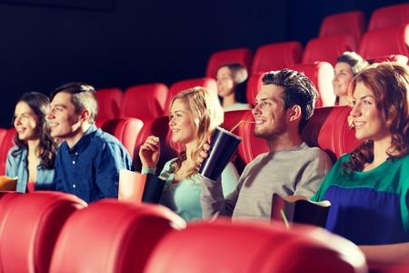 cinta pelicula: el cine, el entretenimiento y la gente concepto - amigos felices viendo la película en el teatro