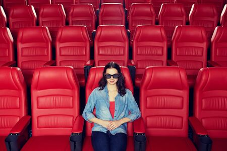 empty of people: cinema, technology, entertainment and people concept - young woman with 3d glasses watching movie alone in empty theater auditorium Stock Photo