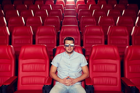 empty of people: cinema, technology, entertainment and people concept - happy young man with 3d glasses watching movie alone in empty theater auditorium Stock Photo