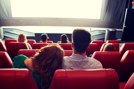 theatre performance: cinema, entertainment, leisure and people concept - happy, couple watching movie in theater from back