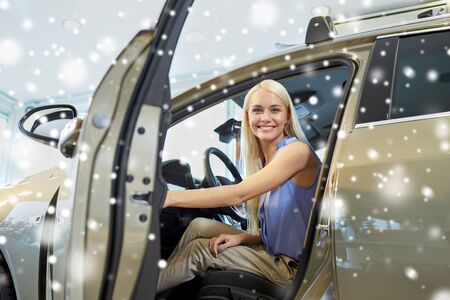 open car door: auto business, car sale, consumerism , transportation and people concept - happy woman sitting in or driving car over snow effect
