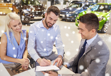 selling service smile: auto business, sale and people concept - happy couple with dealer buying car and signing documents in auto show or salon over snow effect