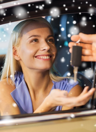 receiving: auto business, car sale, consumerism and people concept - happy woman taking car key from dealer in auto show or salon over snow effect Stock Photo
