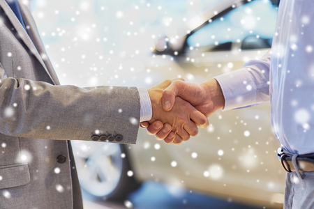 deal in: auto business, car sale, deal, gesture and people concept - close up of male handshake in auto show or salon over snow effect