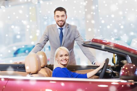 inside car: auto business, car sale, consumerism and people concept - happy couple buying cabrio car in auto show or salon over snow effect