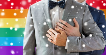 homosexual sex: people, celebration, homosexuality, same-sex marriage and love concept - close up of happy male gay couple with wedding rings hugging over rainbow flag background and snow effect