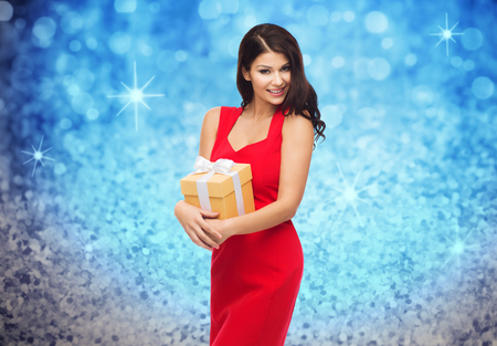 sexy birthday: people, holidays, christmas, birthday and celebration concept - beautiful sexy woman in red dress with gift box over blue glitter and lights background Stock Photo