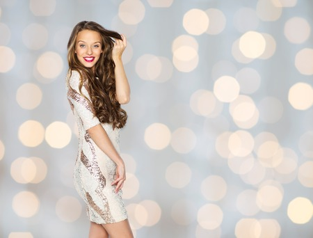 fashion style: people, style, holidays, hairstyle and fashion concept - happy young woman or teen girl in fancy dress with sequins touching long wavy hair over lights background