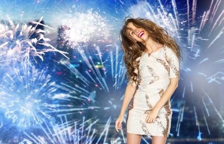 tänzerin: Menschen, Stil, Urlaub, Frisur und Mode-Konzept - glückliche junge Frau oder jugendlich Mädchen im Abendkleid mit Pailletten und langen gewellten Haaren tanzen auf Party über Feuerwerk in der Nacht Stadt Hintergrund
