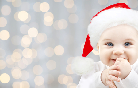 babyhood: christmas, babyhood, childhood and people concept - happy baby in santa hat over holidays lights background Stock Photo