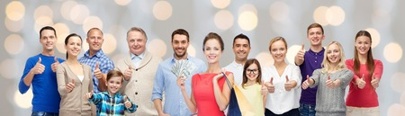 thumbs up group: gesture, sale and people concept - group of smiling men, women and kids showing thumbs up and holding shopping bags with money over holidays lights background Stock Photo