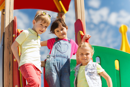 fashion boy: summer, childhood, leisure, friendship and people concept - group of happy kids on children playground