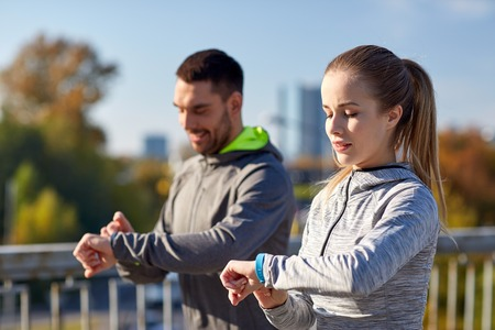 heartrate: fitness, sport, people, technology and healthy lifestyle concept - smiling couple with heart-rate watch running over city highway bridge