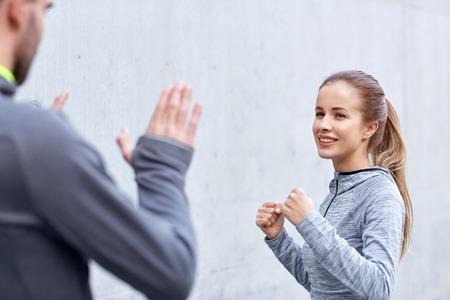defensa personal: fitness, deporte, artes marciales, defensa personal y la gente concepto - mujer feliz con el entrenador personal que se resuelve la huelga al aire libre