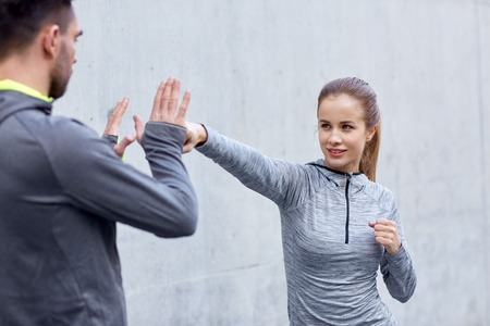defense: fitness, sport, martial arts, self-defense and people concept - happy woman with personal trainer working out strike outdoors Stock Photo