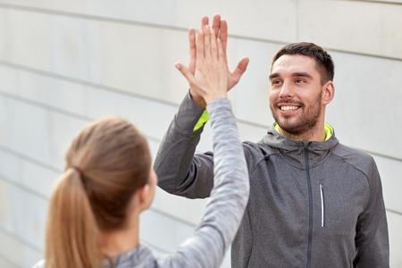 ropa deportiva: fitness, deporte, el gesto, la gente y el concepto de éxito - pareja feliz dando de alta cinco al aire libre Foto de archivo