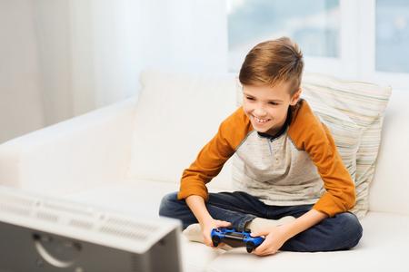 Ocio, los niños, la tecnología y el concepto de la gente - muchacho sonriente con joystick jugando videojuegos en el hogar Foto de archivo - 51334126