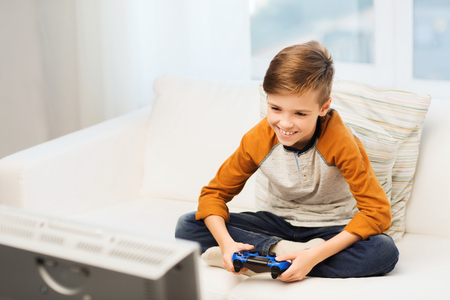 jugando videojuegos: ocio, los niños, la tecnología y el concepto de la gente - muchacho sonriente con joystick jugando videojuegos en el hogar