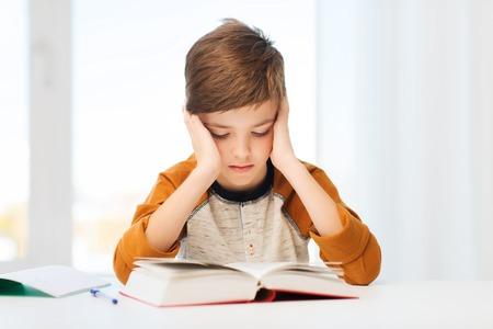 教育、子供のころ、人々、宿題、学校のコンセプト - 本や自宅で教科書を読んで退屈学生少年