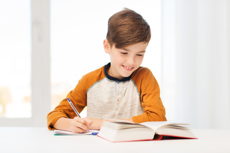 Study Desk: education, childhood, people, homework and school concept - smiling student boy with book writing to notebook at home Stock Photo