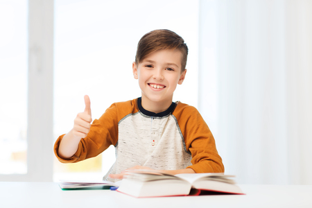 pre approval: education, childhood, people and school concept - happy student boy with textbook and notebook showing thumbs up at home