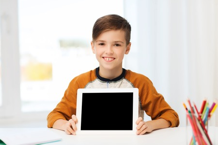 pre teen boy: leisure, children, technology, education and people concept - smiling boy showing empty tablet pc computer screen at home Stock Photo