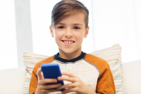 pre adolescent boy: leisure, children, technology, internet communication and people concept - smiling boy with smartphone texting message or playing game at home